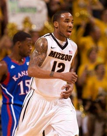 Missouri's Marcus Denmon, right, celebrates in front of Kansas' Elijah Johnson, left, after making a basket during the first half of an NCAA college basketball game Saturday, Feb. 4, 2012, in Columbia, Mo. (AP Photo/L.G. Patterson) By L.G. PATTERSON