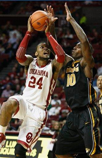 Oklahoma's Romero Osby (24) goes up for a basket as Missouri's Ricardo Ratliffe defends during the second half of an NCAA college basketball game in Norman, Okla. on Monday, Feb. 6, 2012.  Missouri won 71-68.  (AP Photo/Alonzo Adams) By Alonzo Adams