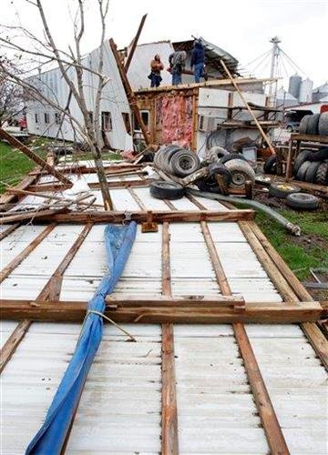 Farm workers secure the roof of a damaged barn in Thorntown, Ind., Wednesday, April 20, 2011.  Overnight storms downed power lines and damaged structures in the area. (AP Photo/Michael Conroy) By Michael Conroy