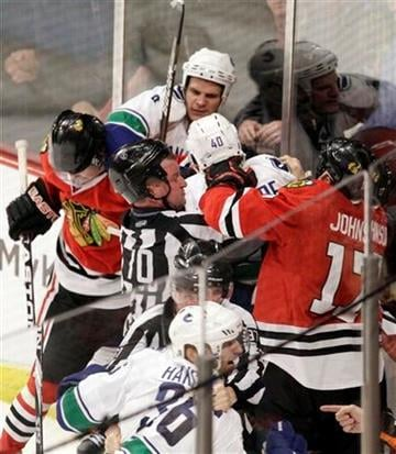 Officials break up a fight during the third period in Game 4 of an NHL hockey Stanley Cup playoffs first-round series between the Chicago Blackhawks and the Vancouver Canucks on Tuesday, April 19, 2011, in Chicago. (AP Photo/Nam Y. Huh) By Nam Y. Huh