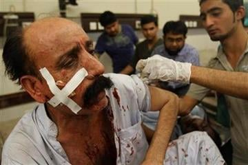 Pakistani hospital staff treat a person injured by bomb blast  ripped through a illegal gambling den in Karachi, Pakistan killing 15 people and wounded many more on Thursday, April 21, 2011, officials said. (AP Photo/Shakil Adil) By Shakil Adil