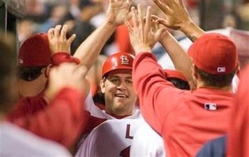 St. Louis Cardinals right fielder Lance Berkman is congratulated after scoring on a single by David Freese during the third inning of a baseball game against the Cincinnati Reds Friday, April 22, 2011, in St. Louis. (AP Photo/Jeff Curry) By Jeff Curry