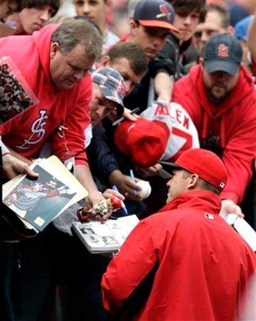 Cincinnati Reds' Scott Rolen, bottom, a former St. Louis Cardinals player, sign autographs for fans before a baseball game against Cardinals, Saturday, April 23, 2011, in St. Louis.(AP Photo/Tom Gannam) By Tom Gannam