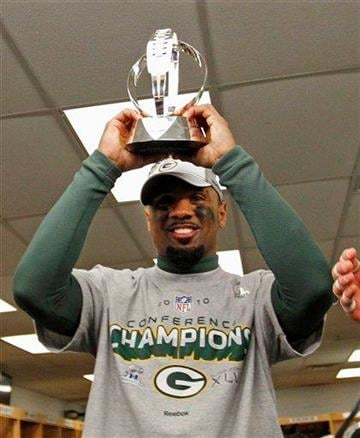 Green Bay Packers cornerback Charles Woodson (21) holds the George Halas Trophy after the NFC Championship NFL football game Sunday, Jan. 23, 2011, in Chicago. The Packers won 21-14. (AP Photo/David J. Philip) By David J. Philip