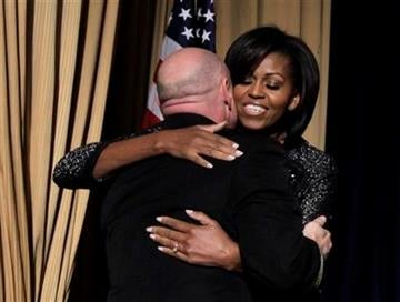 Astronaut Mark Kelly, husband of wounded Rep. Gabrielle Giffords, gets a hug from first lady Michelle Obama at the National Prayer Breakfast in Washington, Thursday, Feb. 3, 2011. (AP Photo/Charles Dharapak) By Charles Dharapak