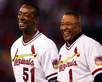 ST. LOUIS - SEPTEMBER 30:  Ozzie Smith #1 and Willie McGee #51 of the 1985 St. Louis Cardinals team stand on the field before the game on September 30, 2005 at Busch Stadium in St. Louis, Missouri.  (Photo by Elsa/Getty Images). By Elsa