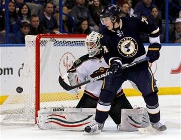 St. Louis Blues' T.J. Oshie, right, and Minnesota Wild goalie Josh Harding keep their eyes on a loose puck during the second period of an NHL hockey game Saturday, Jan. 14, 2012, in St. Louis. (AP Photo/Jeff Roberson) By Jeff Roberson