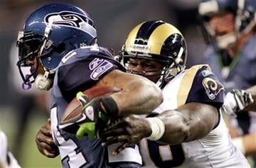 Seattle Seahawks running back Marshawn Lynch (24) is wrapped up by St. Louis Rams' James Hall, right, in the first half of an NFL football game, Monday, Dec. 12, 2011, in Seattle. (AP Photo/Ted S. Warren) By Ted S. Warren