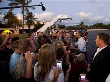 President Barack Obama shakes hands with people waiting to greet him on the tarmac as he steps off of Air Force One at Hickam Air Force Base in Friday, Dec. 23, 2011, in Honolulu. (AP Photo/Carolyn Kaster) By Carolyn Kaster