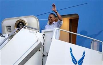 President Barack Obama waves as he steps off of Air Force One at Hickam Air Force Base in Friday, Dec. 23, 2011, in Honolulu. (AP Photo/Carolyn Kaster) By Carolyn Kaster