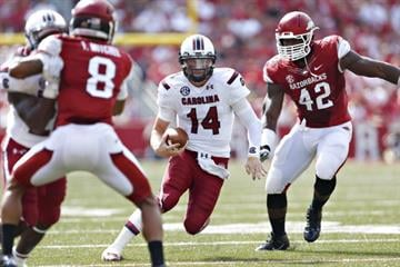 FAYETTEVILLE, AR - OCTOBER 12:  Connor Shaw #14 of the South Carolina Gamecocks runs the ball against the Arkansas Razorbacks at Razorback Stadium on October 12, 2013 in Fayetteville, Arkansas.  (Photo by Wesley Hitt/Getty Images) By Wesley Hitt