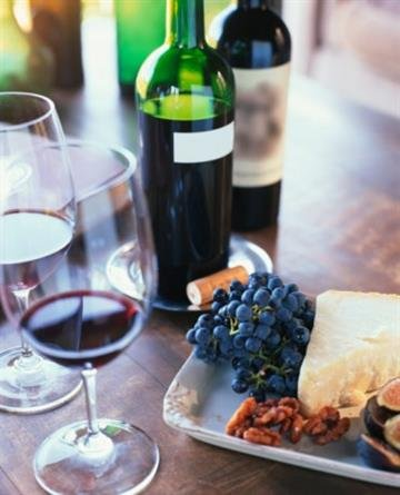 Red wine, fruit, nuts and cheese on table top By Lisa Romerein
