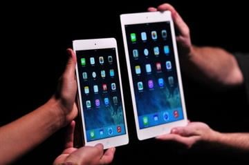 Apple employees show off the new iPad Air (R) and iPad Mini at a satellite launch event in central London on October 22, 2013. AFP PHOTO/CARL COURT        (Photo credit should read CARL COURT/AFP/Getty Images) By CARL COURT