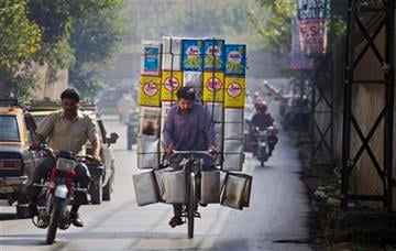 A Pakistani laborer transports empty tin containers of cooking oil on his bicycle at a road in Rawalpindi, Pakistan on Tuesday, Oct. 18, 2011. (AP Photo/Anjum Naveed) By Anjum Naveed