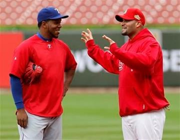 Texas Rangers' Neftali Feliz, left, talks to St. Louis Cardinals' Albert Pujols during practice for Game 1 of baseball's World Series Tuesday, Oct. 18, 2011, in St. Louis. (AP Photo/Eric Gay) By Eric Gay