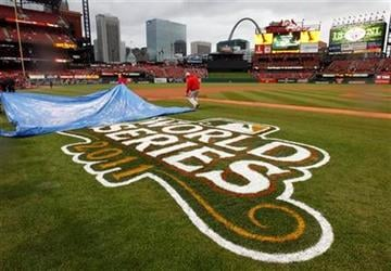 Workers remove a tarp from the third base line before Game 1 of baseball's World Series between the St. Louis Cardinals and the Texas Rangers Wednesday, Oct. 19, 2011, in St. Louis. (AP Photo/Paul Sancya) By Paul Sancya