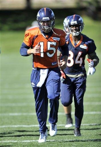 Denver Broncos quarterback Tim Tebow (15) smiles as he runs with wide receiver Brandon Lloyd (84) dduring football practice at the team's training facility, Tuesday, Oct. 11, 2011, in Englewood, Colo.  (AP Photo/Jack Dempsey) By Jack Dempsey