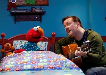 """In this image released by Sesame Workshop, actor-comedian Ricky Gervais sings a lullaby about the letter """"n""""  to character Elmo on the children's program """"Sesame Street,"""" in New York. (AP Photo/Sesame Workshop, Richard Termine) By Richard Termine"""