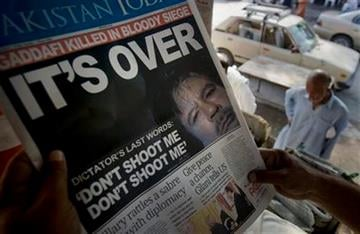 A Pakistani reads a local morning newspaper with the front page featuring a photo and story of Moammar Gadhafi at a newspaper stand in Islamabad, Pakistan on Friday, Oct. 21, 2011. (AP Photo/Andy Wong) By Anjum Naveed