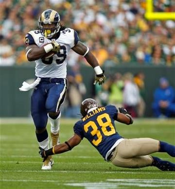 St. Louis Rams defensive back Josh Gordy (39) runs past the reach of Green Bay Packers cornerback Tramon Williams (38) during the first half of an NFL football game Sunday, Oct. 16, 2011, in Green Bay, Wis. (AP Photo/Andy Manis) By Andy Manis