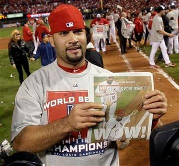 St. Louis Cardinals' Albert Pujols holds up a newspaper after Game 7 of baseball's World Series against the Texas Rangers Friday, Oct. 28, 2011, in St. Louis. The Cardinals won 6-2 to win the series.  (AP Photo/Matt Slocum) By Matt Slocum