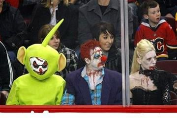 Hockey fans watch the game wearing Halloween costumes as the St. Louis Blues play the Calgary Flames in an NHL hockey game in Calgary, Alberta, Friday, Oct. 28, 2011. (AP Photo/The Canadian Press, Jeff McIntosh) By Jeff McIntosh
