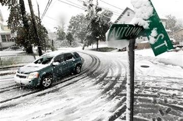 A vehicle makes its way at the snow-covered intersection of Autumn and Grove Streets in Lodi, N.J., following a rare October snowstorm that hit the region, Saturday, Oct. 29, 2011. (AP Photo/Julio Cortez) By Julio Cortez