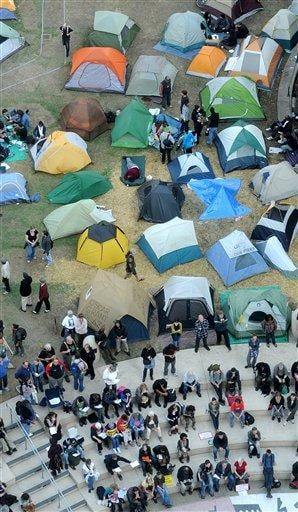Occupy Oakland protesters and their tents line a plaza near Oakland, Calif., City Hall on Friday, Oct. 28, 2011. Demonstrators reestablished the encampment after a police raid on Tuesday left it deserted. (AP Photo/Noah Berger) By Noah Berger