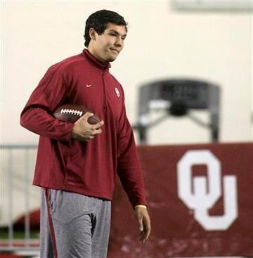 Former Oklahoma quarterback Sam Bradford pauses during warm ups prior to working out for NFL scouts at in Norman, Okla., Monday, March 29, 2010. (AP Photo/Sue Ogrocki) By Sue Ogrocki