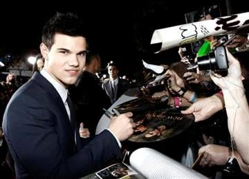 Actor Taylor Lautner signs autographs as he arrives at The Twilight Saga: New Moon premiere in Westwood, Calif. Monday, Nov. 16, 2009.  (AP Photo/Matt Sayles) By Matt Sayles