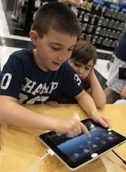 Eight-year-old Matthew Craddock, of Berlington, Ky., and his sister Emma ,5, try out the Apple iPad on the first day of iPad sales, Saturday April 3, 2010 in Florence, Ky. (AP Photo/The Cincinnati Enquirer, Ernest Coleman) By Ernest Coleman