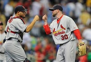 St. Louis Cardinals' Yadier Molina and pitcher Jason Motte (30) celebrate the Cardinals 7-1 victory over the Milwaukee Brewers after a baseball game Saturday, April 10, 2010, in Milwaukee. (AP Photo/Jim Prisching) By Jim Prisching