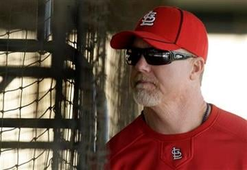 St. Louis Cardinals hitting coach Mark McGwire stands behind a batting cage as he works with Cardinals players during spring training baseball Wednesday, Feb. 17, 2010, in Jupiter, Fla. (AP Photo/Jeff Roberson) By Jeff Roberson