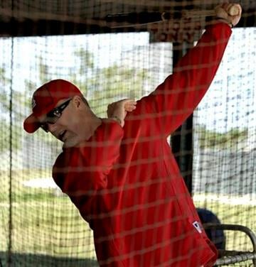 St. Louis Cardinals hitting coach Mark McGwire swings in a batting cage during spring training baseball Wednesday, Feb. 17, 2010, in Jupiter, Fla. (AP Photo/Jeff Roberson) By Jeff Roberson