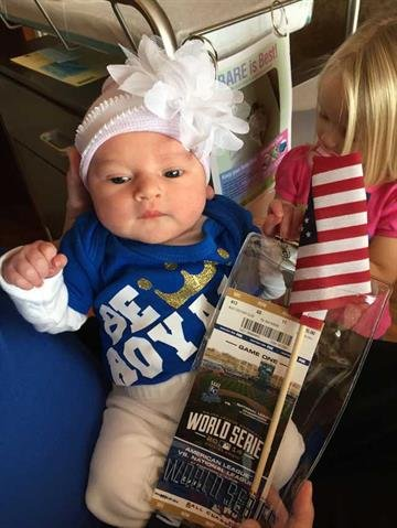 Baby Ali with her parents' World Series Game 1 tickets By KCTV