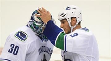 Vancouver Canucks' goalie Ryan Miller (30) is congratulated by Kevin Bieksa (3) after the Canucks' victory 4-1 victory over the St. Louis Blues in an NHL hockey game, Thursday, Oct. 23, 2014, in St. Louis. (AP Photo/Bill Boyce) By Bill Boyce