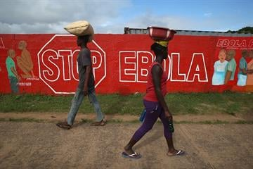 MONROVIA, LIBERIA - OCTOBER 02:  People pass an Ebola awareness mural on October 2, 2014 in Monrovia, Liberia. More than 3,200 people have died in West Africa due to the epidemic.  (Photo by John Moore/Getty Images) By John Moore