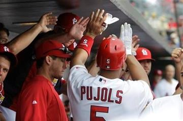 St. Louis Cardinals' Albert Pujols (5) is congratulated by teammates after hitting a double in the ninth inning of a spring training baseball game, Saturday, March 5, 2011 in Jupiter, Fla. (AP Photo/Carlos Osorio) By Carlos Osorio