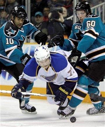 St. Louis Blues' TJ Hensick, center, and San Jose Sharks' Jamal Mayers (10) and Jason Demers (60) fight for the puck during the first period of an NHL hockey game Saturday, March 19, 2011, in San Jose, Calif. (AP Photo/Ben Margot) By Ben Margot