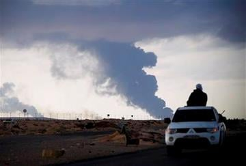 A Libyan volunteer watches smoke rise from the oil port of Sirdra as he leaves in his car on the outskirts of the eastern town of Ras Lanouf, Libya, Wednesday, March 9, 2011. (AP Photo/Tara Todras-Whitehill) By Tara Todras-Whitehill