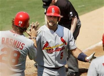 St. Louis Cardinals' Albert Pujols (5) is congratulated at home after a home run in the fifth inning of a spring training baseball game against the Florida Marlins, Saturday, March 26, 2011 in Jupiter, Fla. (AP Photo/Carlos Osorio) By Carlos Osorio