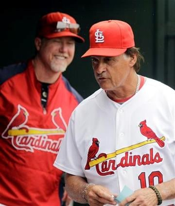 St. Louis Cardinals manager Tony La Russa (10) and batting coach Mark McGwire are seen in the dugout during a spring training baseball game against the Florida Marlins, Monday, March 28, 2011 in Jupiter, Fla. (AP Photo/Carlos Osorio) By Carlos Osorio