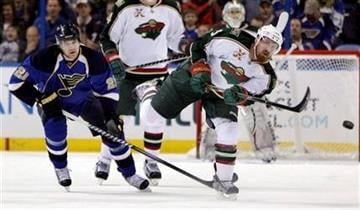 Minnesota Wild's Greg Zanon, right, passes the puck down the ice as St. Louis Blues' Patrik Berglund, of Sweden, looks on during the first period of an NHL hockey game, Tuesday, March 29, 2011, in St. Louis. (AP Photo/Jeff Roberson) By Jeff Roberson