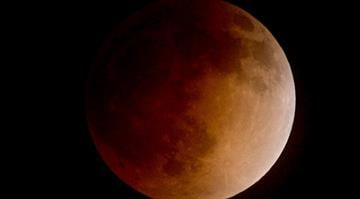 """Sky gazers caught a glimpse of the """"blood moon"""" crossing the Earth's shadow Tuesday in all its splendor. By Kevin Winter"""