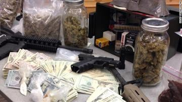 Stacks of cash and semi-automatic weapons are displayed on a table with suspected drugs and dealing equipment. By Brendan Marks
