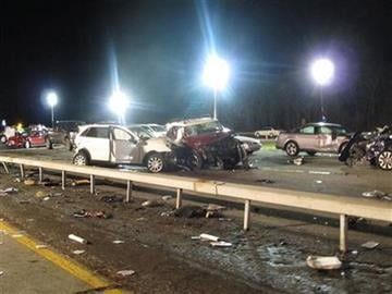 Damaged vehicles and debris are strewn across the Long Island Expressway following a chain reaction crash on Wednesday, Dec. 19, 2012, in Shirley, N.Y. At least one person was killed and 32 injured. (AP Photo/Frank Eltman) By Frank Eltman