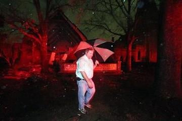 David Webb walks in front of Trinity Episcopal Church on Dauphin St. in Mobile, Ala. on Christmas Day, Tuesday, Dec. 25, 2012. A tornado hit midtown Mobile causing extensive damage to the church. (AP Photo/AL.com, Bill Starling) MAGS OUT By Bill Starling