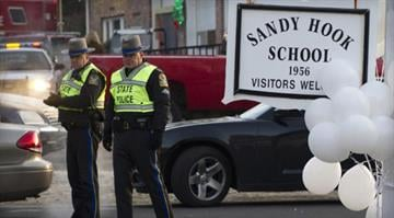 The scene outside Sandy Hook Elementary School in Newtown, Conn., where a gunman killed 26 people, including 20 students ages 6 and 7. / DON EMMERT/Getty Images By Dan Mueller