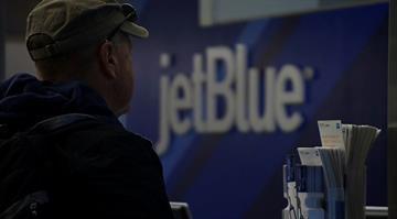 A passenger awaits a JetBlue flight at an unidentified airport. By Stephanie Baumer