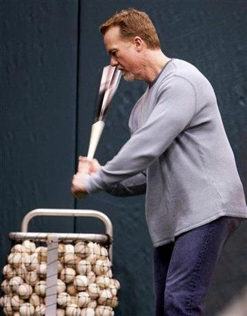 St. Louis Cardinals batting coach Mark McGwire swings a bat as he works with Cardinals outfielder Colby Rasmus in a batting cage Sunday, Jan. 17, 2010, at Busch Stadium in St. Louis. (AP Photo/Jeff Roberson) By Jeff Roberson